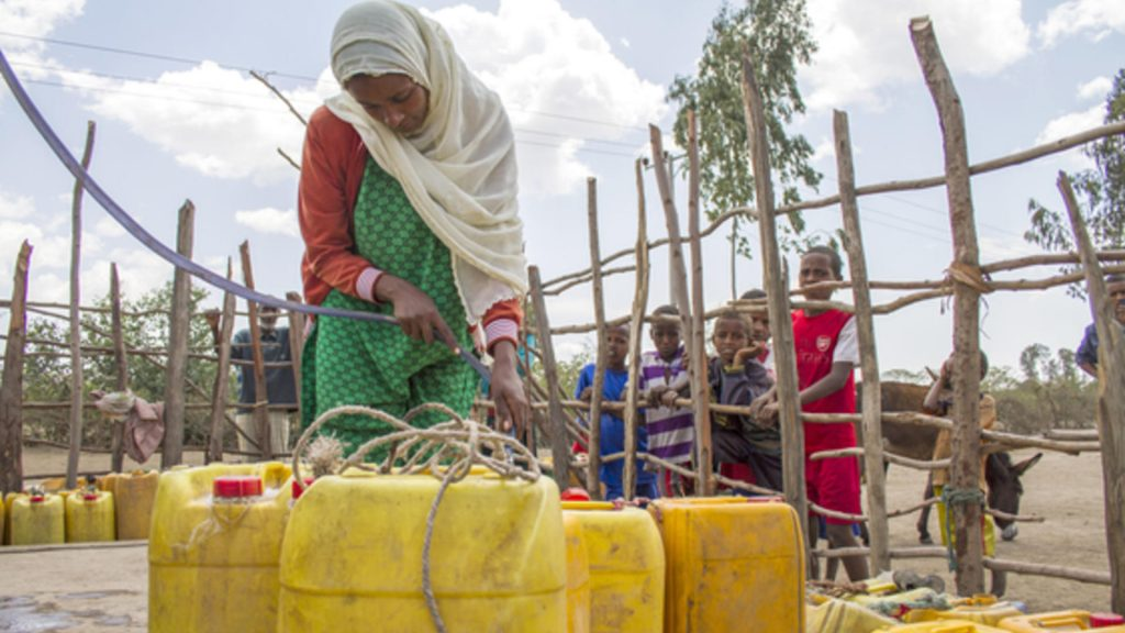 "Meheuba Shifa, 23, and a mother of three, fetches water from an IRC rehabilitated water point in the SNNP region of Ethiopia. Before the water point was rehabilitated, Meheuba walk as far as 6 hours one way to gather enough water at for a single day. The daily 12 hour walk meant she was unable to tend to the rest of her family's needs, causing stress in her home. ""It was a miserable time, I even lost my donkey with the containers while looking for hours for water once. It was an especially heavy burden on me as none of my children are old enough to help me. When we had no water, I had to do all of my work at night, in the dark, when I would come home very tired. Now, [because the water point has been rehabilitated] I can finish my business during the day. My family is peaceful, and I am happy."" Even after gathering water from as far as 6 hours away, the rationed supply -- 40 liters -- was never enough to support her family of five. In order to save water, she would walk two hours away to wash her family's clothes. Woreda: Sankura. ECHO funded."